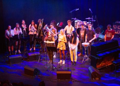 Foto av ungdom som står på en scene med musikkinstrumenter.