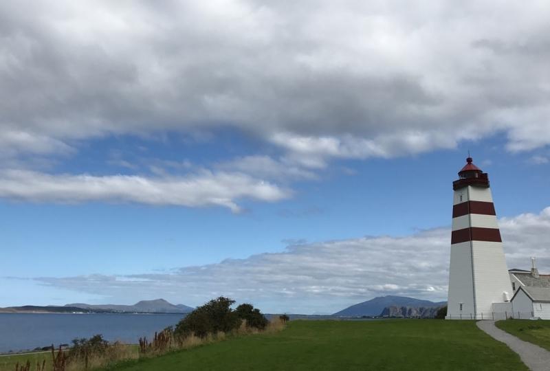 Foto av eit fyr med blå himmel og sjø i bakgrunnen