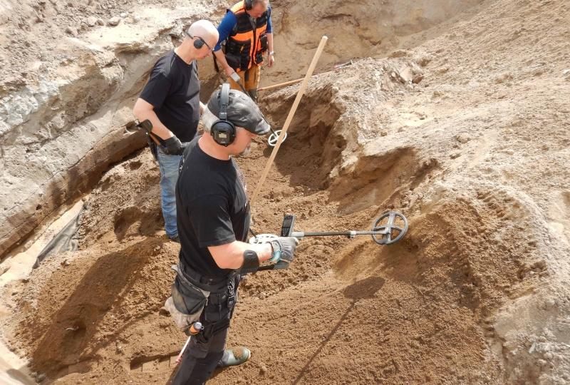 Bilde av tre menn som st¨år med metalldetektor i ei utgraving